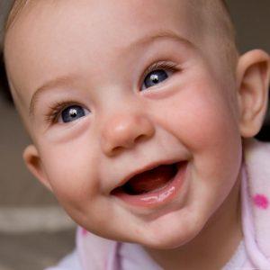 Imagine cu un bebeluş care râde cu gura plină